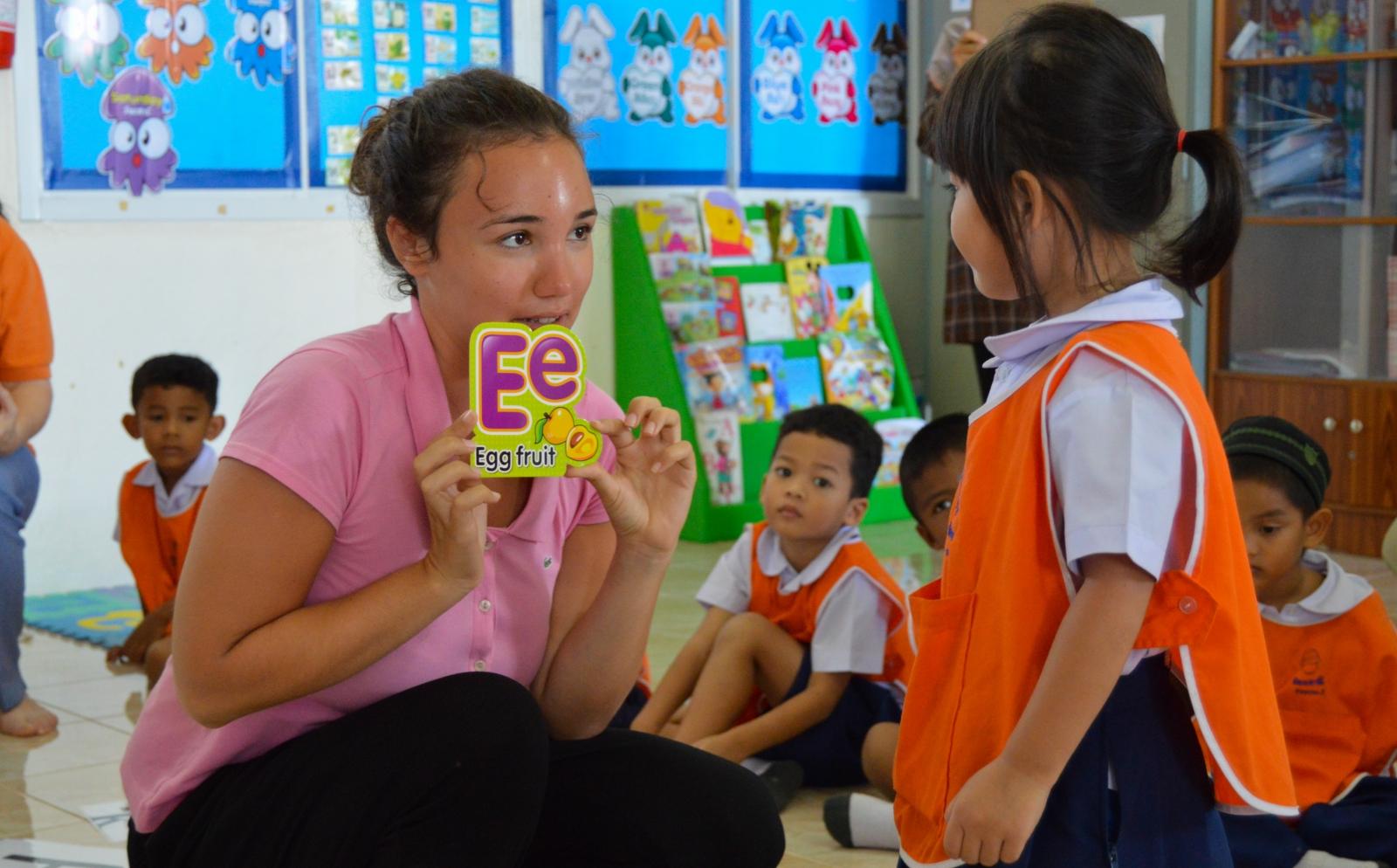 Voluntaria en su año sabático enseñándole a niños el abecedario en Tailandia.